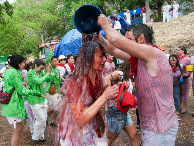 "People pour wine at each other during the traditional ""Battle of Wine"" held as part of the Haro Wine Festival in the La Rioja region in Haro, Spain, 29 June 2016. Every year on 29 June inhabitants and tourists celebrate San Pedro's day by trowing at each other thousands of liters of Riojan wine. (Photo by Abel Alonso/EPA)"