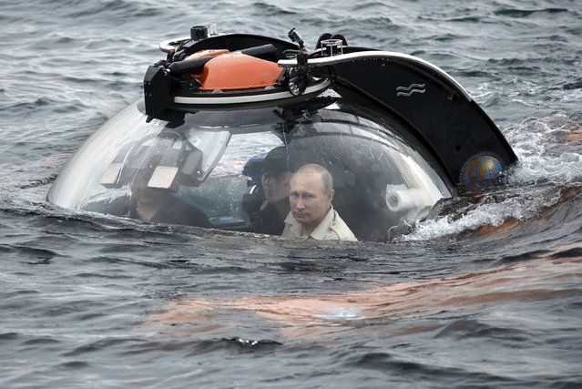 Russian President Vladimir Putin (R) looks through a window of a research bathyscaphe while submerging into the waters of the Black Sea as he takes part in an expedition near Sevastopol, Crimea, August 18, 2015. (Photo by Alexei Nikolsky/Reuters/RIA Novosti/Kremlin)