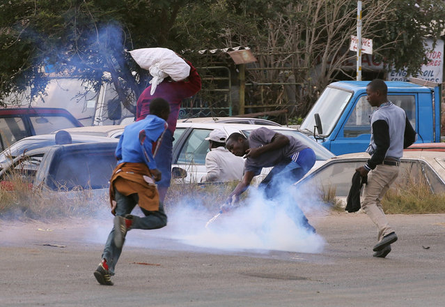 Residents of Epworth suburb flee as riot police fire teargas after a protest by taxi drivers turned violent in Harare, Zimbabwe, July 4,2016. (Photo by Philimon Bulawayo/Reuters)