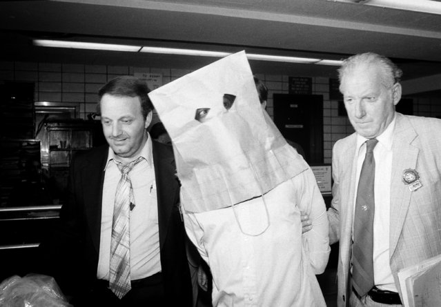 Charles Sears, wearing a bag over his head, is escorted out of the 13th Precinct in New York by detectives after his arrest, July 6, 1981.Sears was arrested in connection with the skid-row slashing deaths of two homeless men and the wounding of 13 others, according to detectives. (Photo by David Bookstaver/AP Photo)