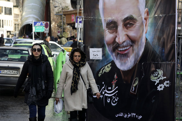 In this January 9, 2020, file photo, women walk past a banner of Iranian Revolutionary Guard Gen. Qassem Soleimani, who was killed in Iraq in a U.S. drone attack, in Tehran, Iran. Iran has had its fingers in Iraq's politics for years, but the U.S. killing of an Iranian general and Iraqi militia commander outside Baghdad has added new impetus to the effort, stoking anti-Americanism that Tehran now hopes it can exploit to help realize the goal of getting U.S. troops out of the country. (Photo by Vahid Salemi/AP Photo/File)