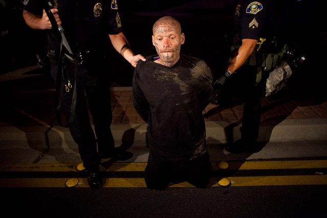 Police officers take a man into custody after he refused to disburse during a demonstration to show outrage for the fatal shooting of Manuel Angel Diaz, 25, at Anaheim City Hall on July 24, 2012 in Anaheim, California. Diaz was fatally shot on July 21 by an Anaheim police officer and has sparked days of protests by the angered community. (Photo by Jonathan Gibby)