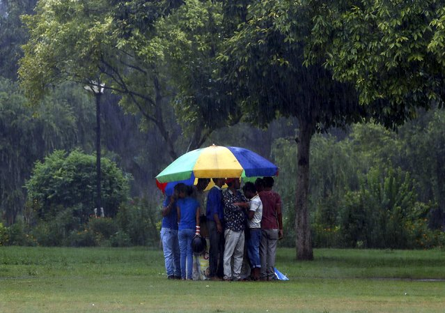 People take shelter under an umbrella of a fast-food seller during a heavy rain shower near India Gate in New Delhi, India, August 21, 2015. (Photo by Anindito Mukherjee/Reuters)