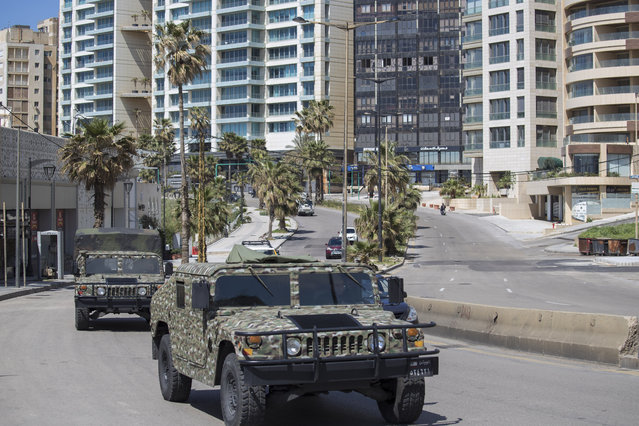Lebanese army vehicles patrol the streets urging people to stay home unless they have to leave for an emergency in an effort to prevent the spread of coronavirus, in Beirut, Lebanon, Sunday, March 22, 2020. (Photo by Hassan Ammar/AP Photo)