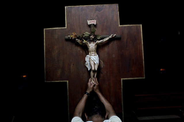 A man prays as he touches a crucifix at La Candelaria church in Caracas, Venezuela, Wednesday, March 13, 2013. (Photo by Rodrigo Abd/AP Photo)