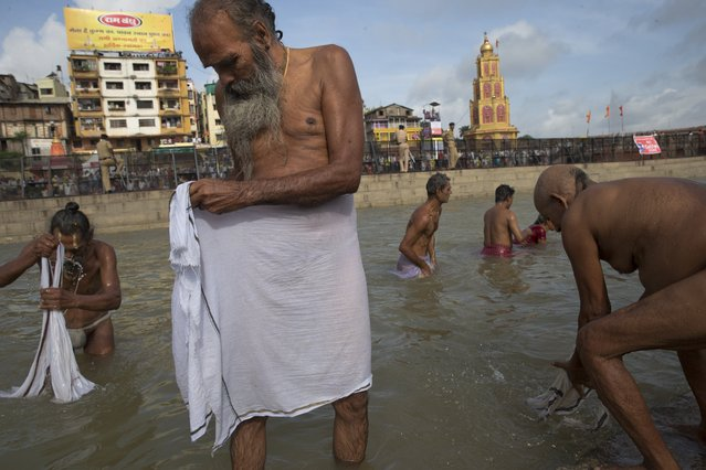 Indian Sadhus, or Hindu holy men bath in the Godavari River during Kumbh Mela, or Pitcher Festival in Nashik, India, Saturday, August 29, 2015. Hindus believe taking a dip in the waters of a holy river during the festival will cleanse them of their sins. (Photo by Tsering Topgyal/AP Photo)