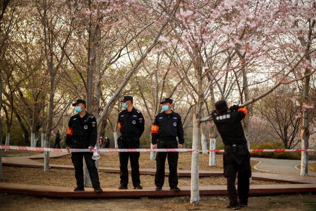 Security guards wear protective masks as they stand under cherry trees in a park in Beijing as the country is hit by an outbreak of the novel coronavirus disease (COVID-19), China, March 23, 2020. (Photo by Thomas Peter/Reuters)