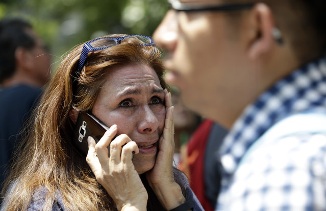 A woman tries to reach people on her cellphone after she evacuated with others to Paseo de la Reforma Avenue after an earthquake in Mexico City, Tuesday, September 19, 2017. A powerful earthquake jolted central Mexico on Tuesday, causing buildings to sway sickeningly in the capital on the anniversary of a 1985 quake that did major damage. (Photo by Marco Ugarte/AP Photo)