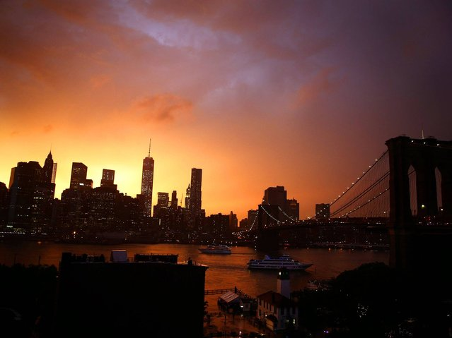 The sun sets behind the Lower Manhattan skyline in New York, USA, 02 July 2014. The US National Weather Service has issued a flash flood watch for parts of New York and New Jersey from early 02 July to 03 July 2014. (Photo by Andrew Gombert/EPA)