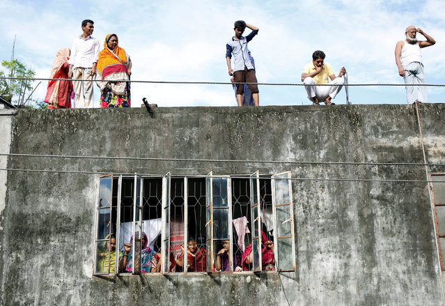 Residents watch from rooftops after a police operation on militants on the outskirts of Dhaka, Bangladesh, July 26, 2016. (Photo by Mohammad Ponir Hossain/Reuters)