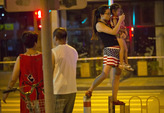 A woman holds a child as she stands on a traffic barrier to take a photo of preparations for a military parade in Beijing, Wednesday, September 2, 2015. (Photo by Mark Schiefelbein/AP Photo)