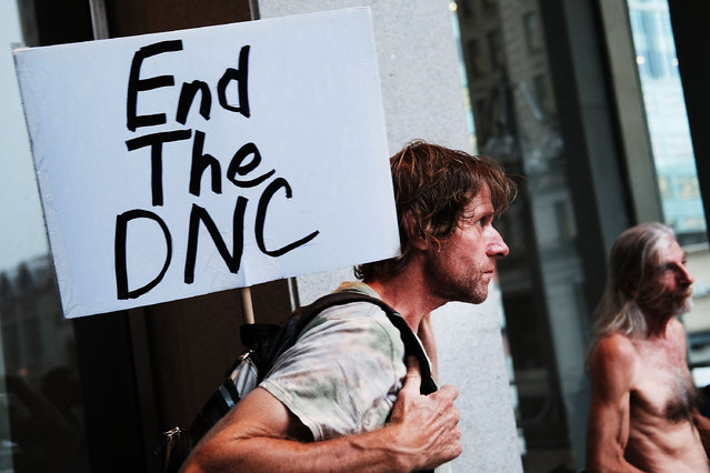 A man holds a sign critical of the Democratic National Convention (DNC) during events at the DNC on July 28, 2016 in Philadelphia, Pennsylvania. (Photo by Spencer Platt/Getty Images)