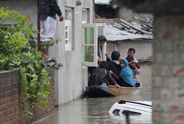 A Kashmiri girl boards a boat from the window of her home as she leaves her flooded neighborhood in Srinagar, India, Thursday, September 4, 2014. (Photo by Mukhtar Khan/AP Photo)
