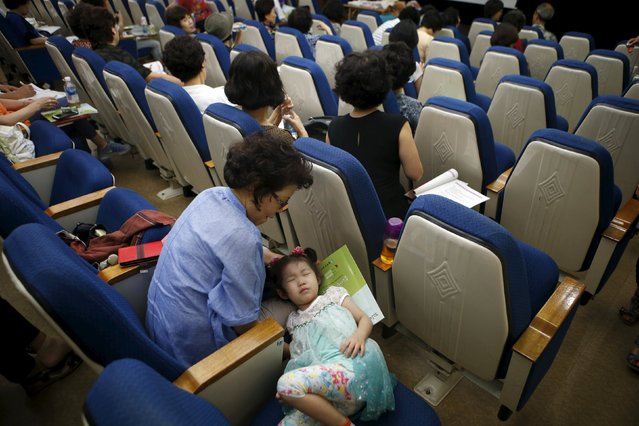 A girl takes a nap next to her grandmother during a child care class for grandparents in Seoul, South Korea, September 1, 2015. (Photo by Kim Hong-Ji/Reuters)
