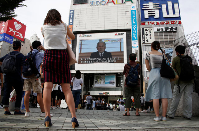 People watch a large screen showing Japanese Emperor Akihito's video address in Tokyo, Japan, August 8, 2016. (Photo by Kim Kyung-Hoon/Reuters)