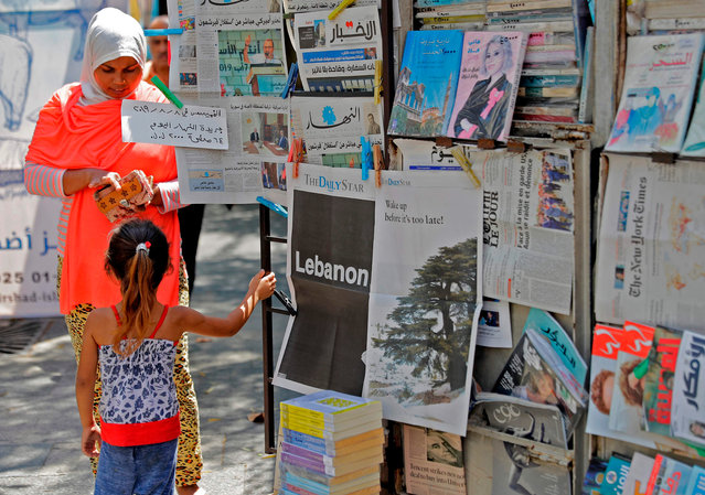 "A girl stands next to a copy of the Lebanese local English-language newspaper ""The Daily Star"" in the capital Beirut on August 8, 2019, which refrained from publishing news articles in its print edition today in protest against the ""deteriorating situation"" in Lebanon. A special edition was printed with each page listing one main issue dragging the country toward the abyss. Despite the worsening political, economic, financial and social problems, there is still time to save the country, the Daily Star, which was first established in the 1950s, announced. (Photo by Joseph Eid/AFP Photo)"