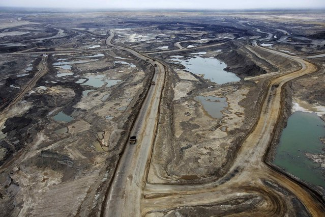 Giant dump trucks haul raw tar sands to be processed at the Suncor tar sands mining operations near Fort McMurray, Alberta, September 17, 2014. (Photo by Todd Korol/Reuters)