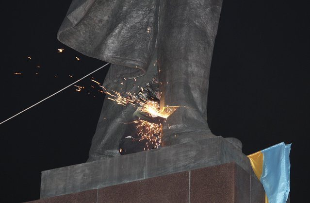 An activist dismantles Ukraine's biggest monument to Lenin at a pro-Ukrainian rally in the central square of the eastern city of Kharkiv, Ukraine, Sunday, September 28, 2014. (Photo by Sergey Kozlov/AP Photo)