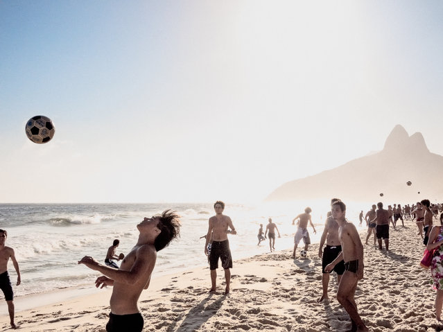"""Ipanema beach, Rio de Janeiro. """"Every afternoon, kids form small groups and kick a soccer ball around playing altinha, an afternoon ritual right up until sunset. Vidigal mountain is the backdrop"""". (Photo by David Alan Harvey/The Guardian)"""
