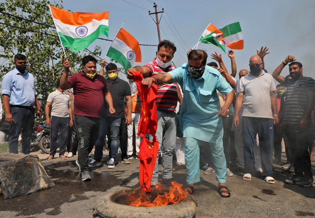 Demonstrators burn a flag resembling Chinese national flag during a protest against China, in Jammu, June 17, 2020. India and China sought Wednesday to de-escalate tensions following a fatal clash along a disputed border high in the Himalayas that left 20 Indian soldiers dead. The skirmish Monday in the desolate alpine area of Ladakh, in Kashmir, followed changes by India to the political status of Kashmir amid a geopolitical tug-of-war with the United States in the region. (Photo by Mukesh Gupta/Reuters)