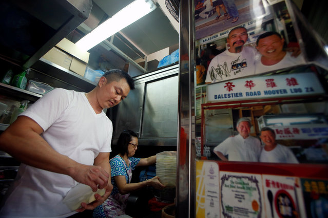 "Hawker Stan Lim, 43, prepares his ingredients at Michelin Bib-Gourmand-awarded Balestier Road Hoover Rojak, at Whampoa Food Centre in Singapore August 12, 2016. The photograph (R) shows Hong Kong celebrity Chow Yun-Fat (top left) posing with Stan's father, Lim Ngah Chew, as Stan opened his doors for business. ""Many of hawkers here at this food centre... told me to find something better outside and not be a hawker because its very hard work, long hours and very little rest"", he said. ""But I took over my father three years ago because he was getting old. I do everything exactly he does, including how I arrange my utensils"". (Photo by Edgar Su/Reuters)"