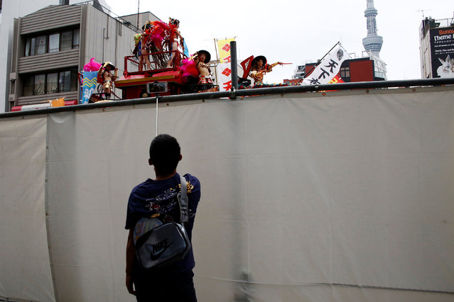 A man takes picture of samba dancers'  performance over a wall during the annual Asakusa Samba Carnival in Tokyo, Japan,  August 27, 2016. (Photo by Kim Kyung-Hoon/Reuters)