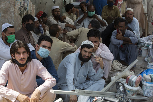 Unmasked daily wage workers wait to be hired by customers in Rawalpindi, Pakistan, June 12, 2020. Pakistan ranks among countries hardest hit by the coronavirus with infections soaring beyond 18,000, while the government, which has opened up the country hoping to salvage a near collapsed economy, warns a stunning 1.2 million Pakistanis could be infected by the end of August. (Photo by B.K. Bangash/AP Photo)