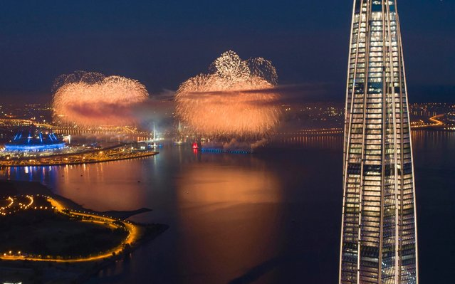 In this aerial photo a brig with scarlet sails, center, travels and fireworks explode at the Finnish Gulf coast during the Scarlet Sails festivities marking school graduation in St. Petersburg, Russia, early Sunday, June 28, 2020, with business tower Lakhta Centre, the headquarters of Russian gas monopoly Gazprom on the right. This year the festival is not to be held in the city center, but on the Finnish Gulf due to the coronavirus pandemic. There are no spectators but the event is broadcast on television. (Photo by Dmitri Lovetsky/AP Photo)
