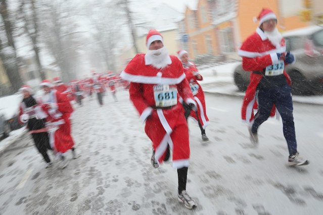 Participants dressed as Santa Claus run through falling snow in the 4th annual Michendorf Santa Run (Michendorfer Nikolauslauf) on December 9, 2012 in Michendorf, Germany. Over 800 people took part in this year's races that included children's and adults' races.  (Photo by Sean Gallup)