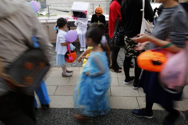 Participants in costumes give candies to children during a Halloween parade in Kawasaki, south of Tokyo, October 26, 2014. (Photo by Yuya Shino/Reuters)