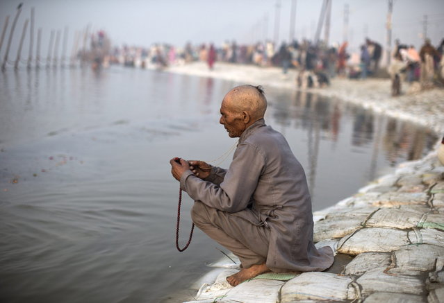 "A Hindu devotee holds a prayer bead on the banks of the river Ganges ahead of the ""Kumbh Mela"" (Pitcher Festival) in the northern Indian city of Allahabad January 13, 2013. During the festival, Hindus take part in a religious gathering on the banks of the river Ganges. The ""Kumbh Mela"" will return to Allahabad in 12 years. (Photo by Ahmad Masood/Reuters)"
