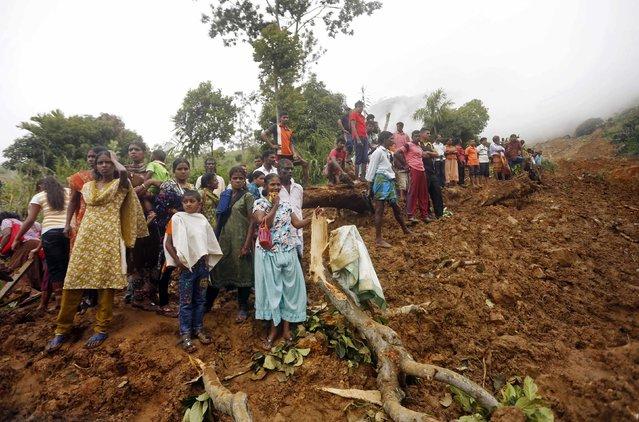 Villagers gather at the site of a landslide at the Koslanda tea plantation near Haldummulla October 30, 2014. (Photo by Dinuka Liyanawatte/Reuters)