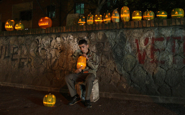 A boy sells pumpkins carved as grimacing faces with candles inside in a street of Tirana on October 30, 2014, one day before Halloween. (Photo by Gent Shkullaku/AFP Photo)
