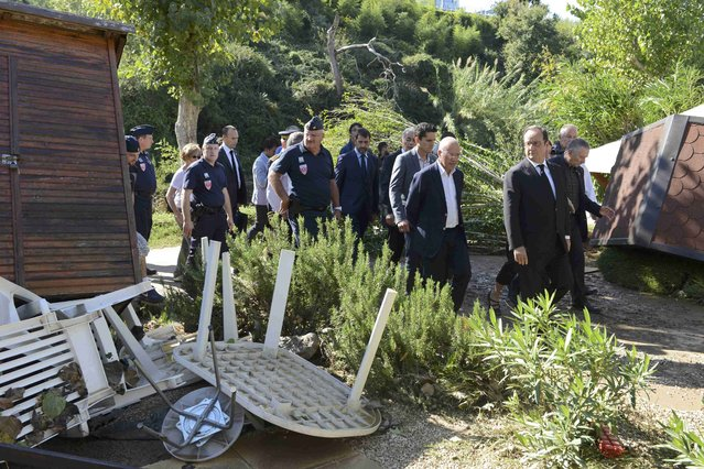 French President Francois Hollande (R) walks near debris during his visit to the Camping du Pylone site to observe damage after flooding caused by torrential rain in Biot, France, October 4, 2015. Flooding along part of the French Riviera has killed at least 16 people, officials said Sunday. The downpour hit the Alpes-Maritimes region, which lies at the eastern end of France's Mediterranean coast and borders Italy, on Saturday evening. (Photo by Jean-Pierre Amet/Reuters)