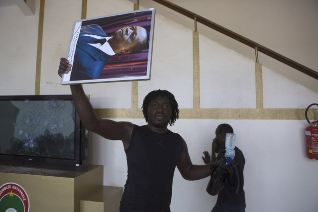 An anti-government protester carries a poster of President Blaise Compaore in the parliament building in Ouagadougou, capital of Burkina Faso, October 30, 2014. (Photo by Joe Penney/Reuters)
