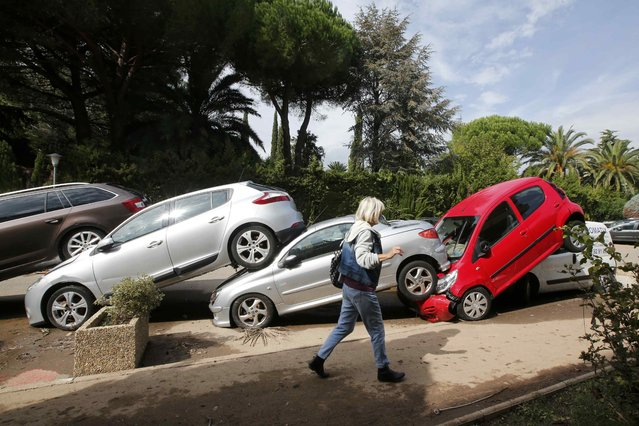A woman walks past cars which are stacked one against another outside a residential apartment building the day after torrential rains caused flooding in Mandelieu-La Napoule, France, October 5, 2015. Two people were still missing on Monday after flash floods on the French Riviera killed at least 19 people over the weekend, prompting the government to declare a natural disaster in the southeastern tourist region. (Photo by Jean-Paul Pelissier/Reuters)