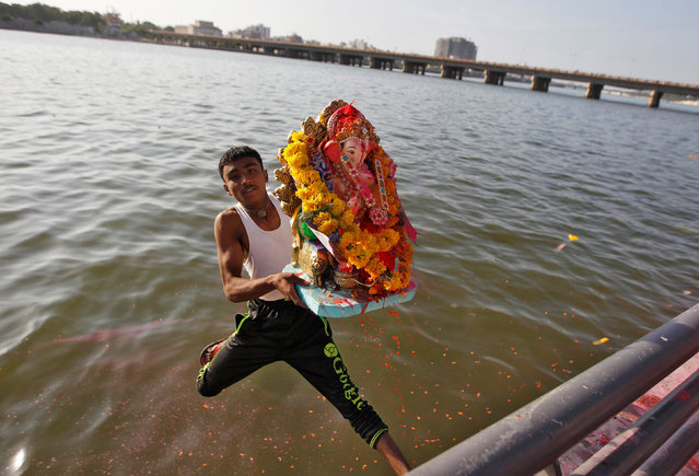 A devotee carrying an idol of the Hindu god Ganesh, the deity of prosperity, jumps into the Sabarmati river to immerse the idol during the 10-day-long Ganesh Chaturthi festival in Ahmedabad, India, September 11, 2016. (Photo by Amit Dave/Reuters)