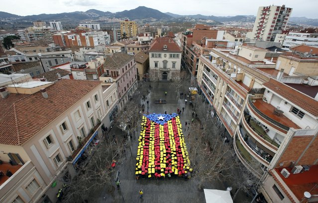 People hold placards to form a giant Estelada, the Catalan separatist flag, in front of the Sant Feliu del Llobregat townhall, near Barcelona February 16, 2014. (Photo by Albert Gea/Reuters)