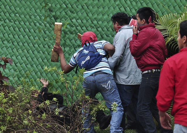 A man beats a police officer lying on the ground during a protest in reprisal for the killing of 43 trainee teachers, in Acapulco November 10, 2014. According to the government, corrupt police in league with a local drug gang abducted and apparently murdered the students in the southwestern sate of Guerrero in late September. (Photo by Claudio Vargas/Reuters)