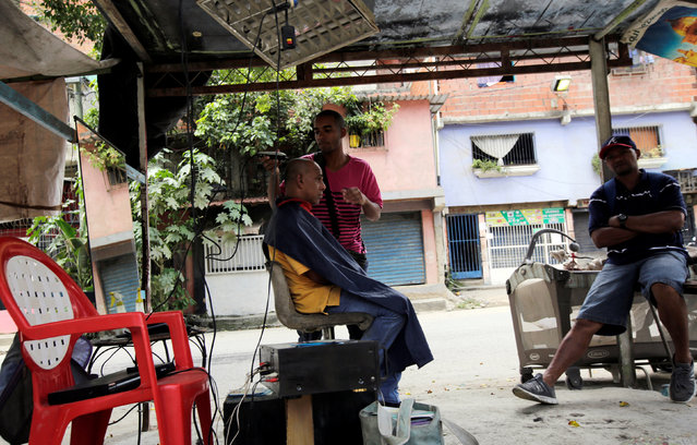 A barber cuts hair at an open air barber shop along a sidewalk in the low-income neighborhood of Caucaguita in Caracas, Venezuela September 17, 2016. (Photo by Henry Romero/Reuters)