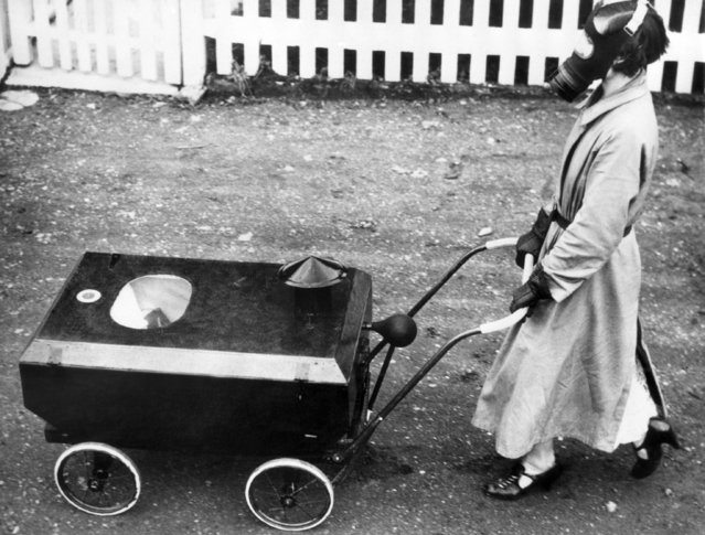 This gas-masked nurse is pushing a baby carriage, although it looks like a field kitchen, there's a baby in it, in London, on December 22, 1938. Its inventor, E.W. Mills of Huxtable, Kent, England, says it is gas-proof, it works on the same principle as the mask worn by the nurse. Mills thought it up during the war scare. (Photo by AP Photo)