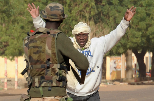 A Malian soldier arrests a man at a checkpoint one day after Islamist gunmen battled French and Malian troops, on February 11, 2013 in Gao. (Photo by Pascal Guyot/AFP Photo/The Atlantic)