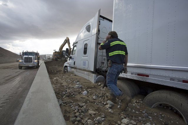 A man walks past cars and trucks mired in mud and debris on State Route 58 near Tehachapi, California, about 60 miles (97 km) outside of Los Angeles October 17, 2015. (Photo by David McNew/Reuters)