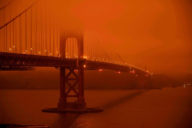 """Cars drive along the San Francisco Bay Bridge under an orange smoke filled sky at midday in San Francisco, California on September 9, 2020. More than 300,000 acres are burning across the northwestern state including 35 major wildfires, with at least five towns """"substantially destroyed"""" and mass evacuations taking place. (Photo by Harold Postic/AFP Photo)"""