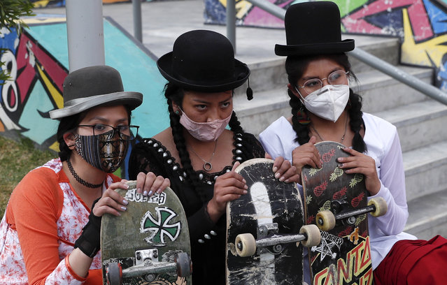 """Yanira Villarreal, left, Ayde Choque, center, and Milenda Limachi, wearings masks amid the COVID-19 pandemic and dressed as a """"Cholita"""" pose for a photo with their skateboards during a youth talent show in La Paz, Bolivia, Wednesday, September 30, 2020. Young women called """"Skates Imillas"""", using the Aymara word for girl Imilla, use traditional Indigenous clothing as a statement of pride of their Indigenous culture while playing riding their skateboards. (Photo by Juan Karita/AP Photo)"""