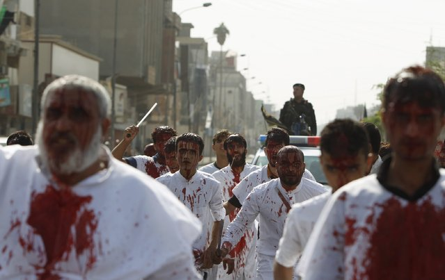 Iraq Shi'ite Muslim men bleed as they gash their foreheads with swords and beat themselves during commemoration Ashura in Baghdad, October 24, 2015. (Photo by Ahmed Saad/Reuters)