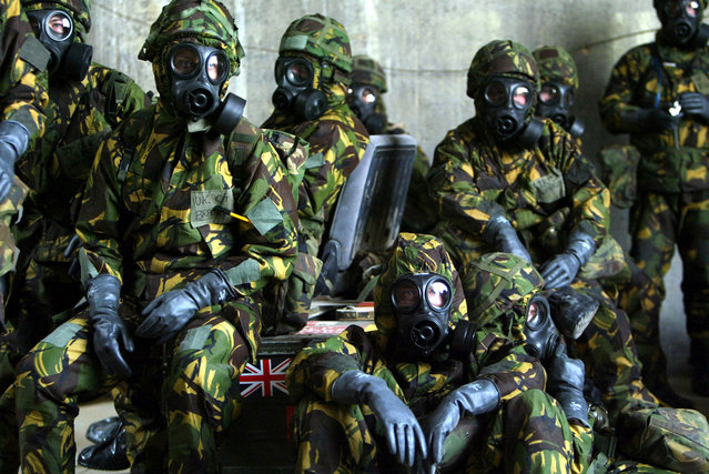 British Royal Air Force personnel wait in a bunker wearing full Nuclear Biological and Chemical suits after a warning of a Scud missile attack on their base in Kuwait March 20, 2003. (Photo by Russell Boyce/Reuters/The Atlantic)