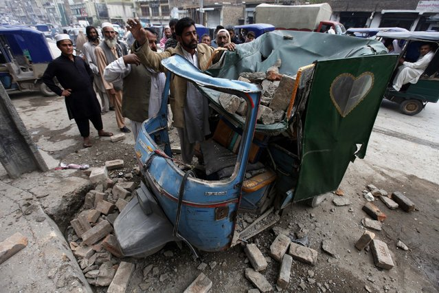People remove debris from a rickshaw on a road following a 7.7 magnitude earthquake, in Peshawar, Pakistan, 26 October 2015. A strong earthquake with a magnitude of 7.7 hit northern Afghanistan's Hindu Kush mountain range causing damage in Pakistan and India as well. At least 69 people were killed in Pakistan, 20 in Afghanistan and hundreds wounded. (Photo by Arshad Arbab/EPA)