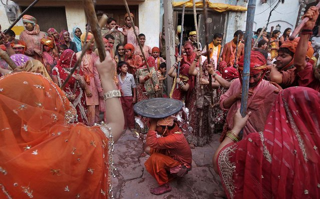 Indian women from Nandgaon hit villagers from Barsana. During Lathmar Holi the women of Nandgaon, the hometown of Krishna, beat the men from Barsana, the legendary hometown of Radha, consort of the Hindu God Krishna, with wooden sticks in response to their teasing as they depart the town. (Photo by Manish Swarup/Associated Press)