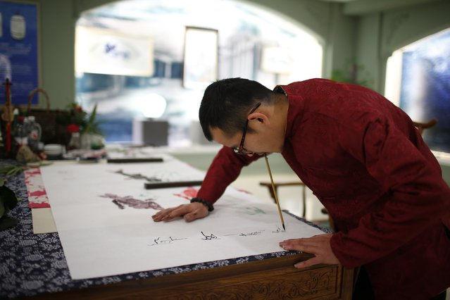 Folk artist Han Xiaoming demonstrates painting with his mouth in Hangzhou, Zhejiang province December 4, 2014. (Photo by Aly Song/Reuters)